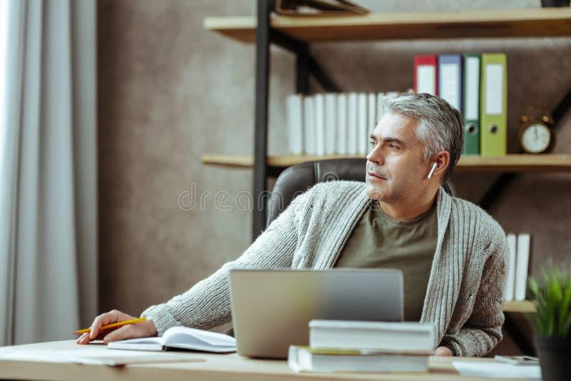 Hombre pensativo agradable que mira en la ventana imágenes de archivo libres de regalías