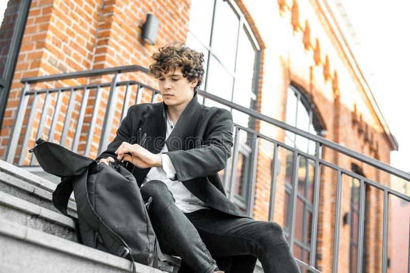 Hombre pensativo atractivo joven que se sienta en pasos y que revuelve en su mochila imágenes de archivo libres de regalías