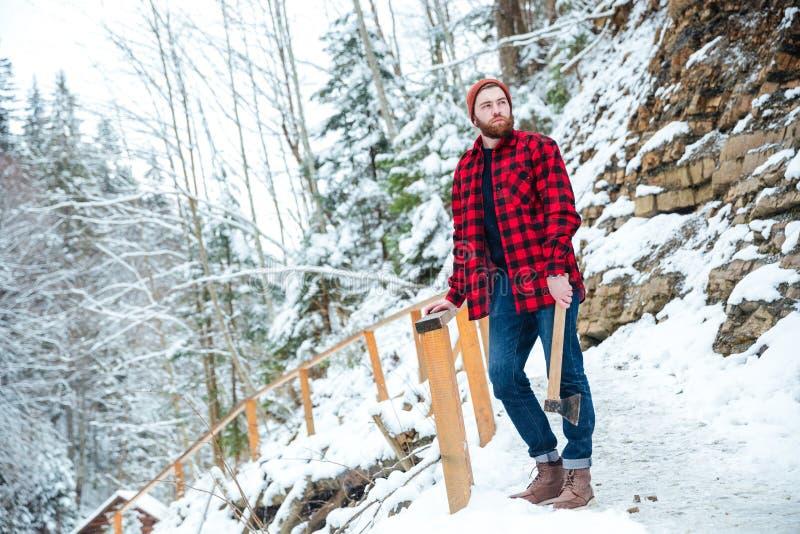 Hombre pensativo con la barba que sostiene el hacha en las montañas en invierno fotografía de archivo