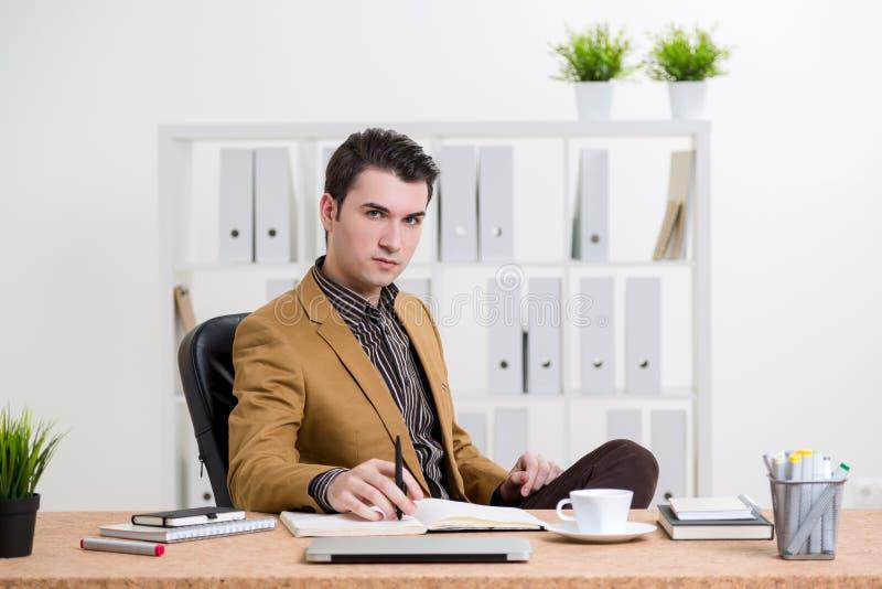 Hombre pensativo en el escritorio de oficina foto de archivo