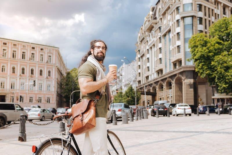 Hombre pensativo hermoso que sostiene una taza con café fotos de archivo