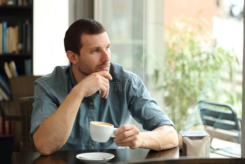 Hombre pensativo mirando al aire libre a través de una ventana imagenes de archivo