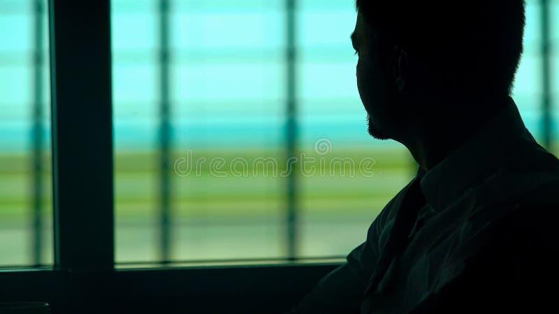 Hombre pensativo que come la taza de café en sala de espera, agujereada con rutina diaria imagenes de archivo