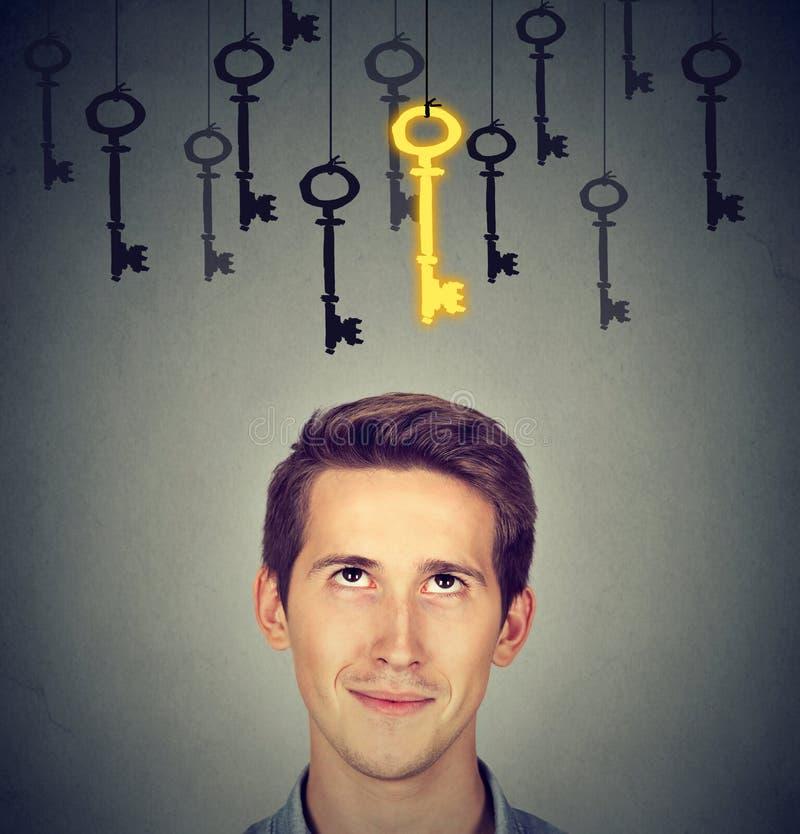 Hombre pensativo que considera para arriba la llave de oro del vintage al éxito entre muchos otros la ejecución fotografía de archivo