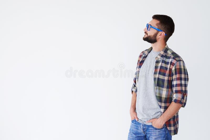 Hombre pensativo que lleva a cabo las manos en los bolsillos que miran el espacio de la copia foto de archivo libre de regalías