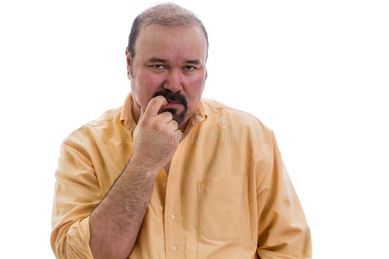Hombre pensativo que mastica su finger como él discute imagen de archivo