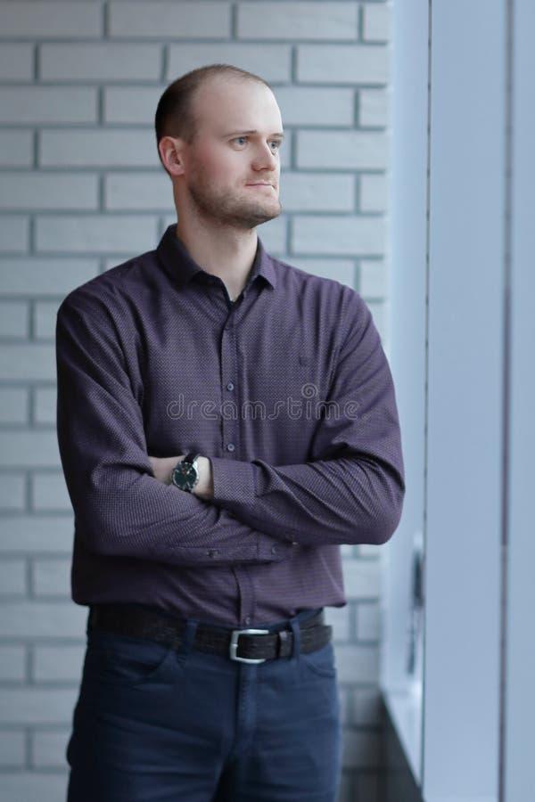 Hombre pensativo que piensa en algo detr?s de las persianas foto de archivo libre de regalías