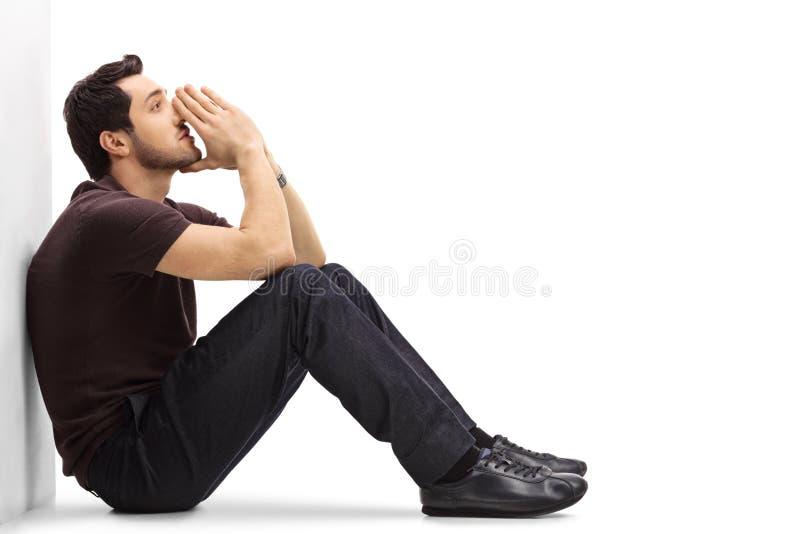 Hombre pensativo que se inclina contra una pared y un pensamiento fotos de archivo