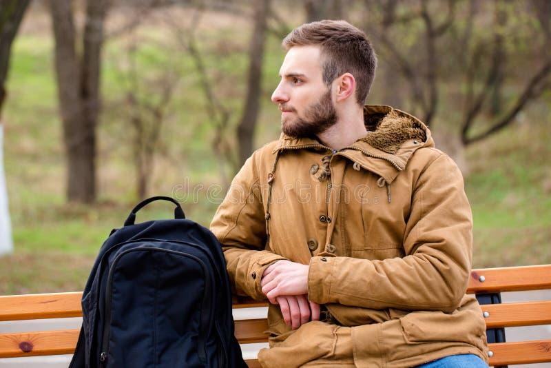 Hombre pensativo que se sienta en el banco al aire libre fotos de archivo