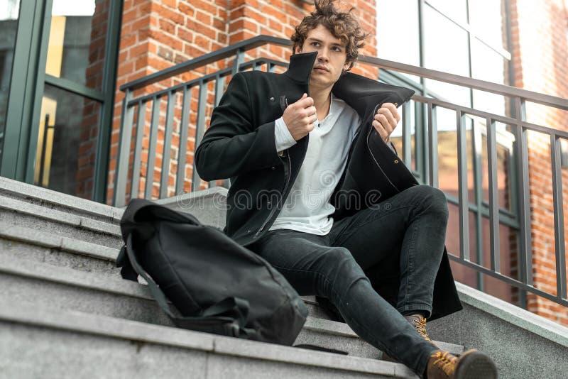 Hombre pensativo que se sienta en pasos concretos y que envuelve para arriba en capa negra fotografía de archivo