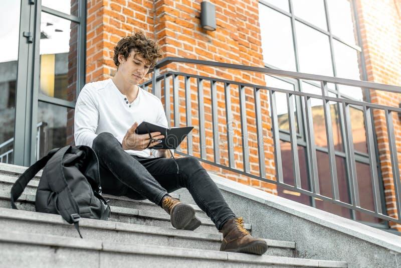 Hombre pensativo que se sienta en pasos concretos y que hace notas en su libreta foto de archivo