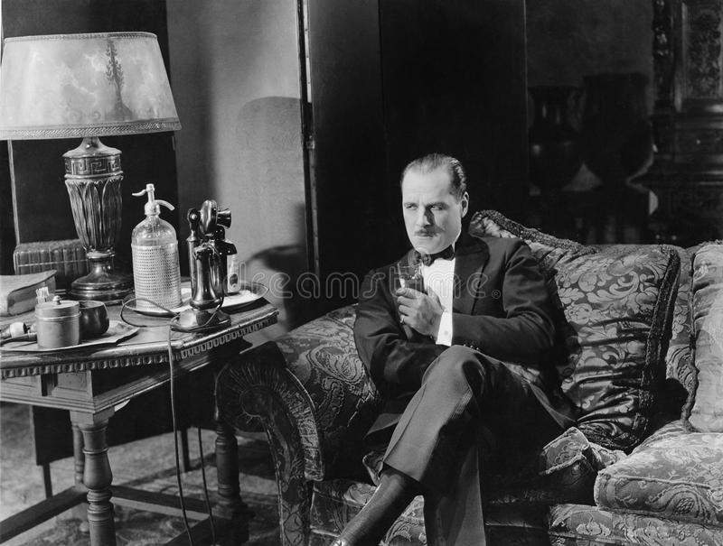 Hombre pensativo que tiene una bebida en el sofá foto de archivo