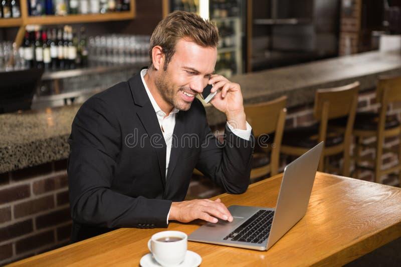 Hombre pensativo que usa el ordenador portátil y teniendo una llamada de teléfono foto de archivo libre de regalías