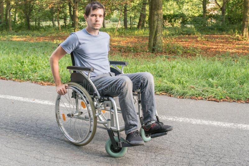 Hombre perjudicado o discapacitado de los jóvenes en la silla de ruedas fotografía de archivo libre de regalías