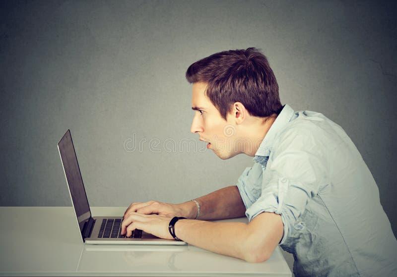 Hombre perplejo chocado que se sienta delante del ordenador portátil que mira la pantalla fotos de archivo
