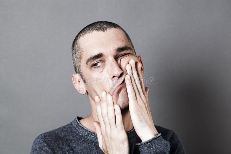 Hombre perplejo extraño que actúa aburrido y perturbado, jugando con la cara fotos de archivo
