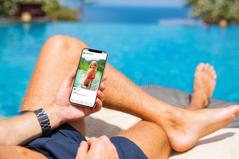 Hombre por la piscina que mira los medios sociales app en su teléfono móvil imagenes de archivo