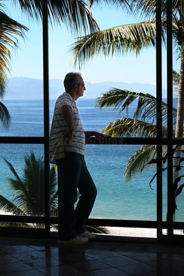 Hombre por la ventana imagen de archivo