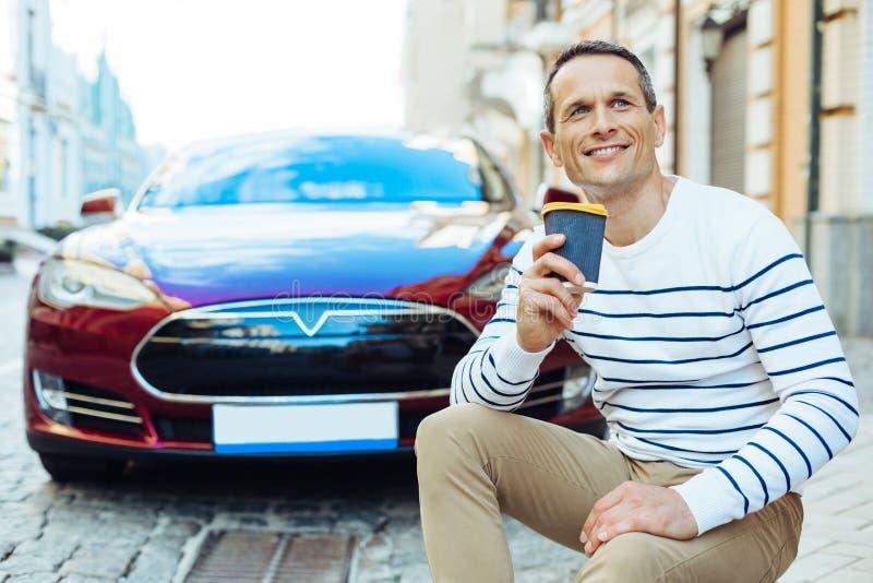 Hombre positivo alegre que sostiene una taza con café imagen de archivo libre de regalías