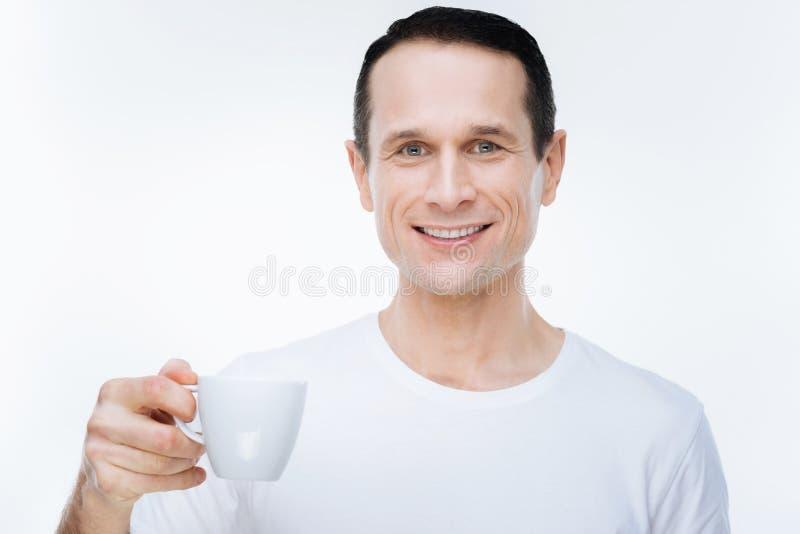 Hombre positivo alegre que sostiene una taza de café imagen de archivo