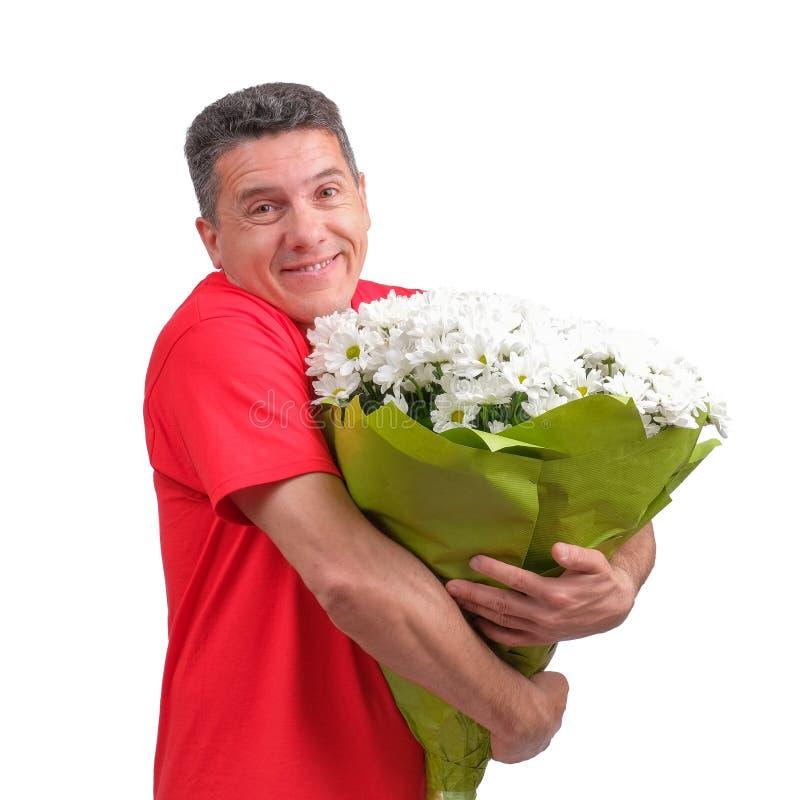 Hombre positivo confuso que lleva la camiseta informal roja con el ramo en sus manos foto de archivo