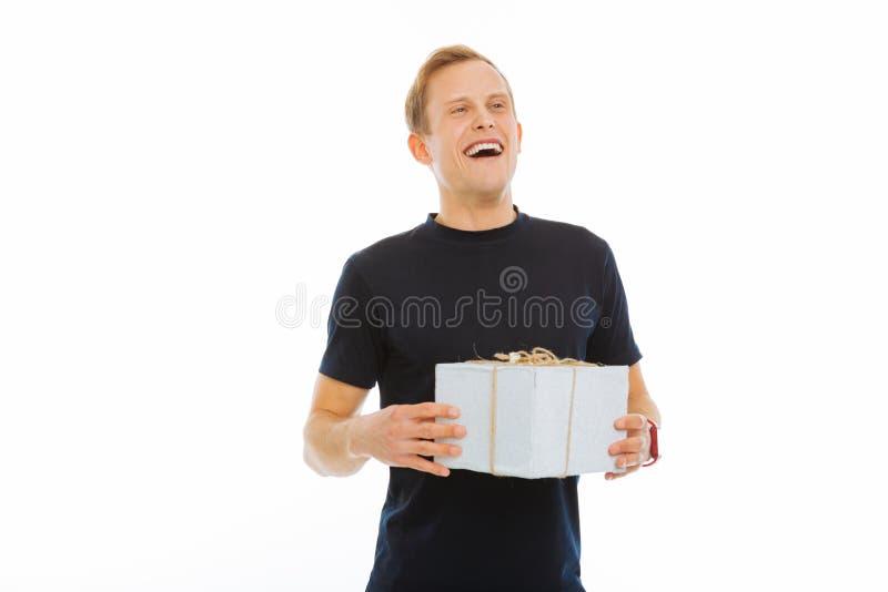 Hombre positivo encantado que recibe un presente de cumpleaños fotos de archivo