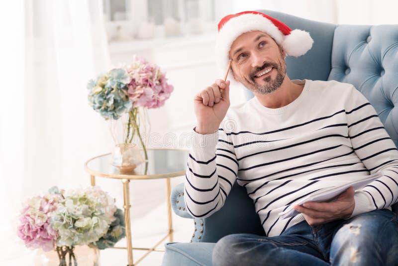 Hombre positivo feliz que escribe una lista de presentes imagen de archivo