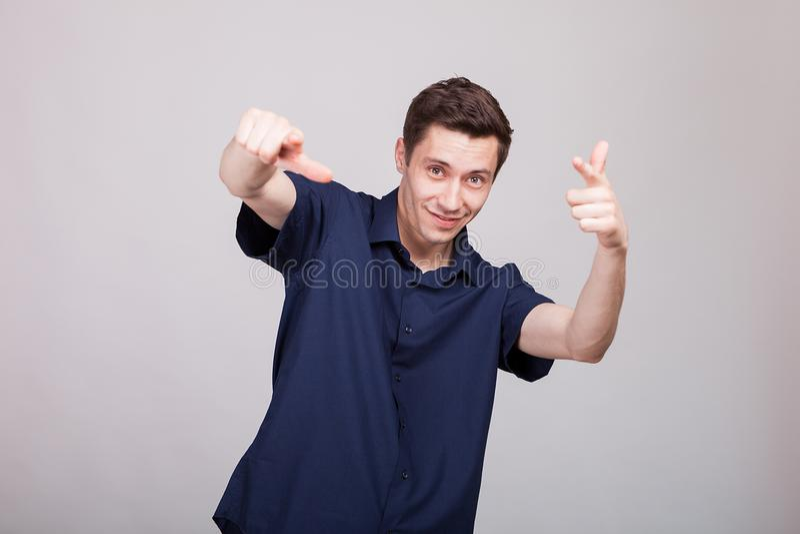 Hombre positivo joven que hace caras del sillu imágenes de archivo libres de regalías