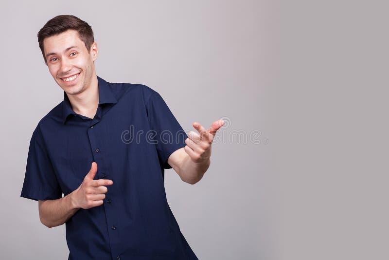 Hombre positivo joven que hace caras del sillu fotos de archivo