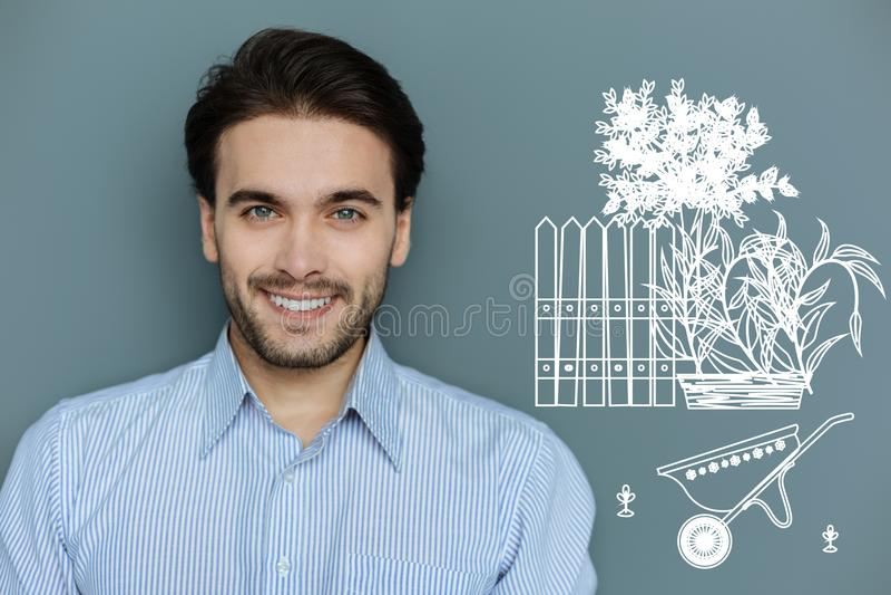 Hombre positivo que sonríe mientras que sueña sobre un nuevo jardín imágenes de archivo libres de regalías