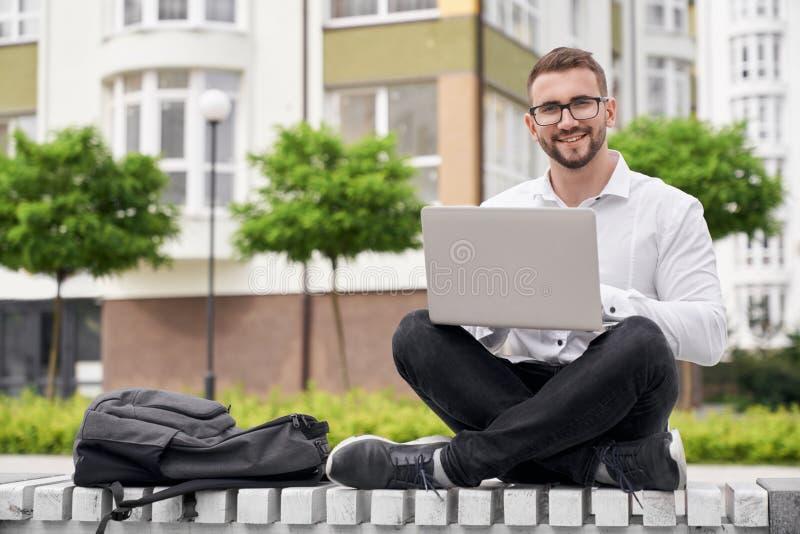 Hombre positivo que trabaja en el banco al aire libre en ciudad, usando el ordenador portátil fotografía de archivo