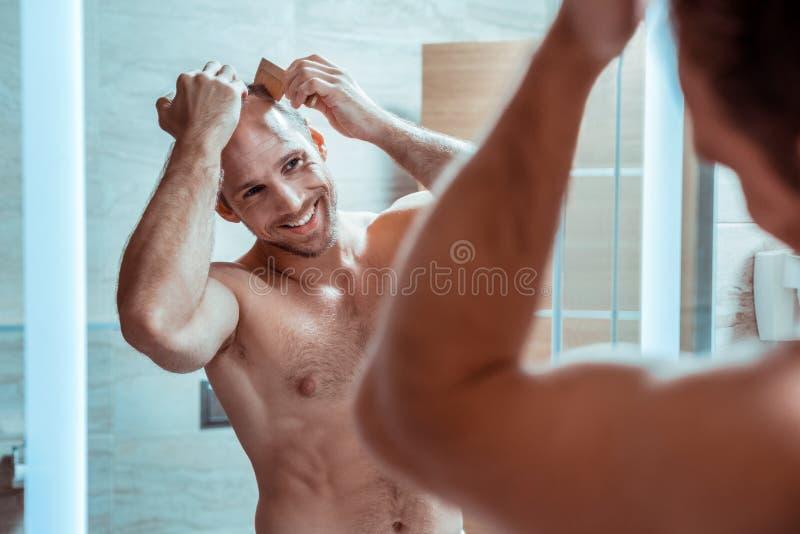 Hombre positivo sonriente que está en gran humor por la mañana fotografía de archivo libre de regalías
