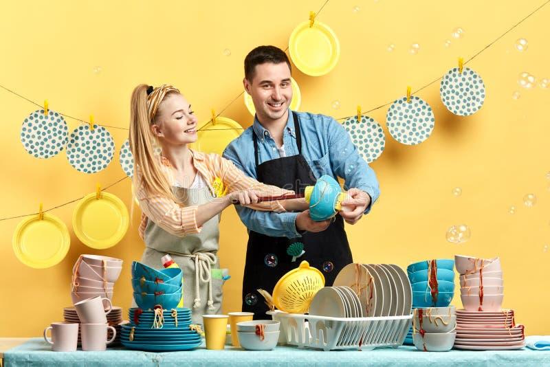 Hombre positivo y mujer que gozan lavando los platos imágenes de archivo libres de regalías