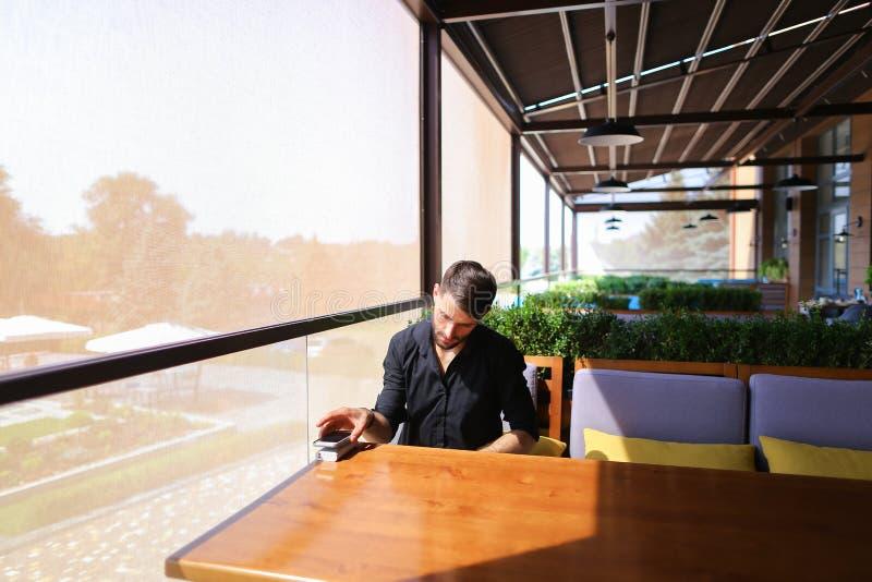 Hombre próspero que usa el smartphone para la conversación un banco a del poder foto de archivo
