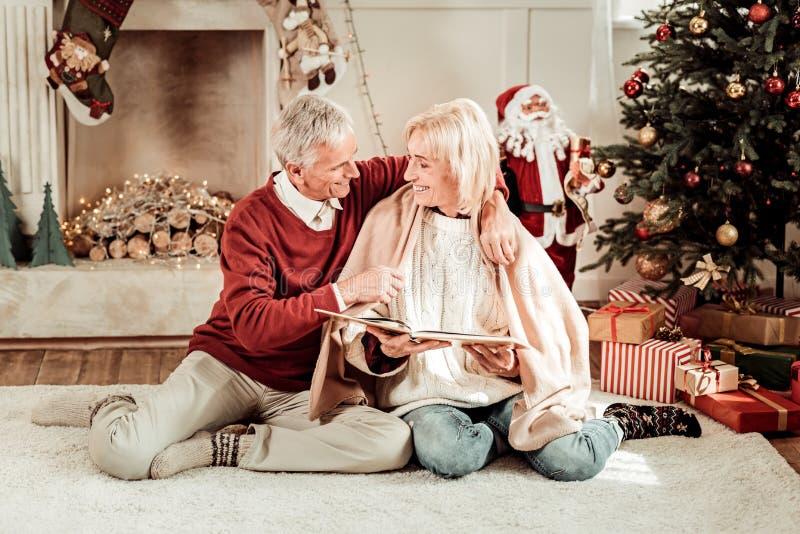 Hombre precioso que cuida que sienta y que abraza a su esposa foto de archivo