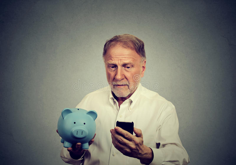 Hombre preocupado que mira su teléfono móvil que sostiene la hucha fotografía de archivo libre de regalías