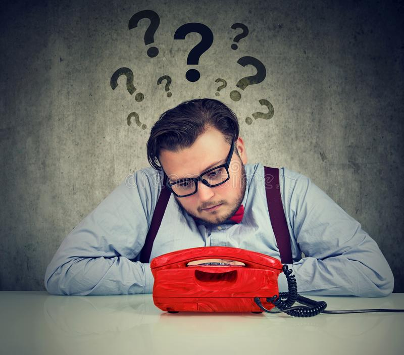 Hombre preocupante con demasiadas preguntas que esperan una llamada imágenes de archivo libres de regalías