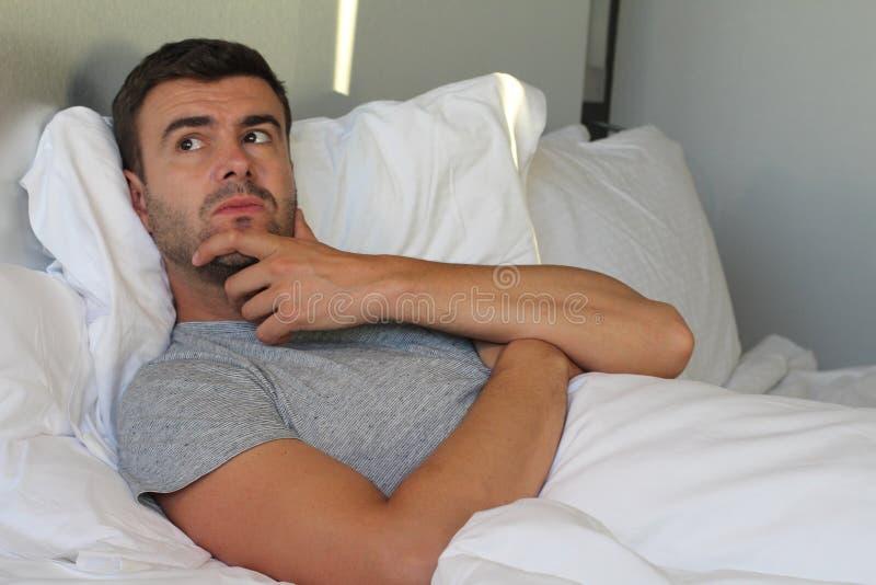 Hombre preocupante overthinking en cama foto de archivo