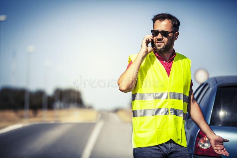 Hombre preocupante que habla con la compañía de seguros después de avería del coche imagen de archivo libre de regalías