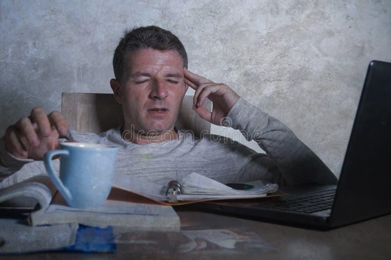 Hombre preocupante y desesperado que trabaja en casa el escritorio de última hora con el papeleo que considera frustrado y cansad foto de archivo libre de regalías