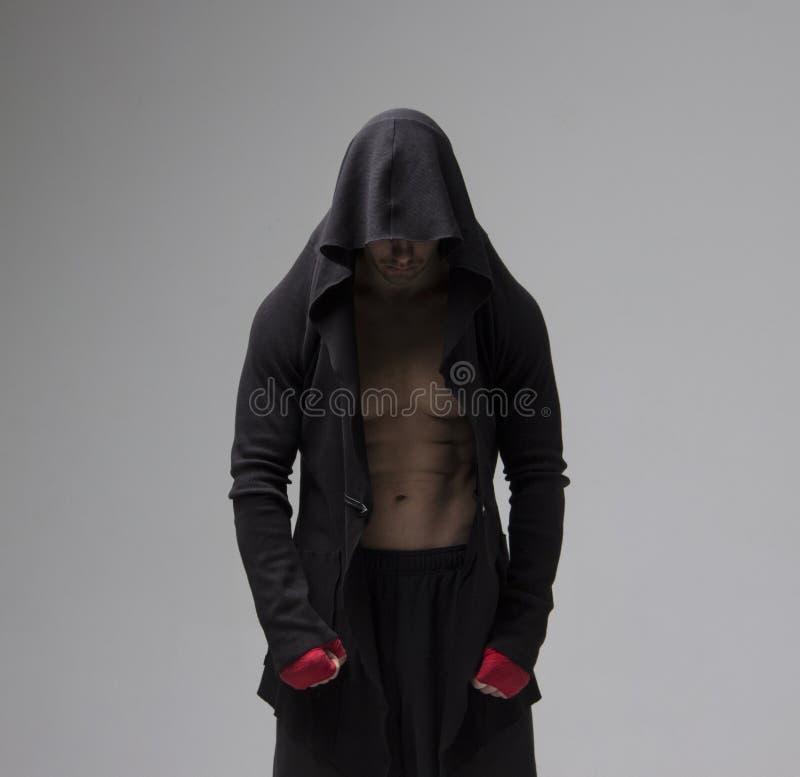 Hombre preparado concentrado del combatiente en la ropa de deportes que mira abajo imágenes de archivo libres de regalías