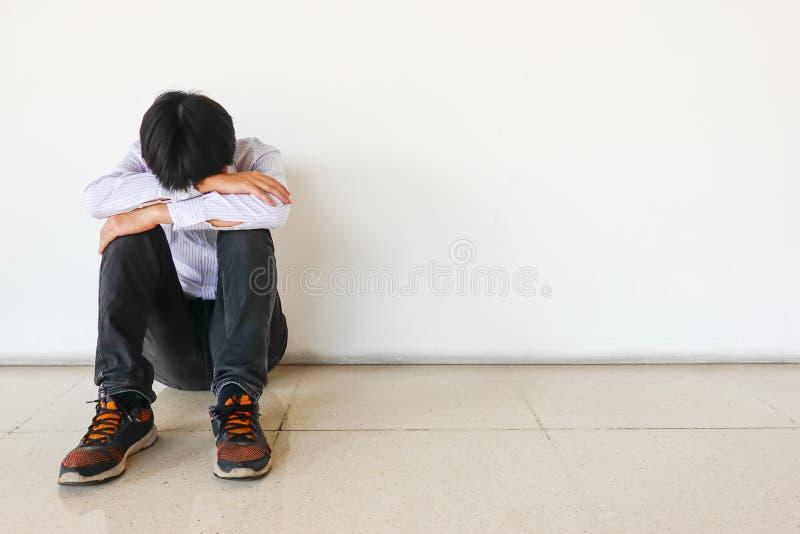 Hombre presionado que se sienta contra una pared y una cabeza en manos en el piso, hombre triste, grito, concepto del drama fotografía de archivo libre de regalías