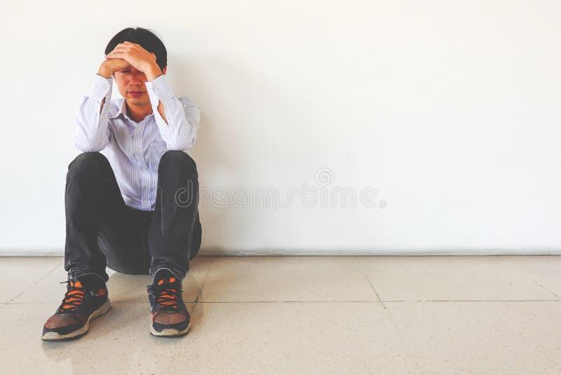 Hombre presionado que se sienta contra una pared y una cabeza en manos en el piso, hombre triste, grito, concepto del drama foto de archivo