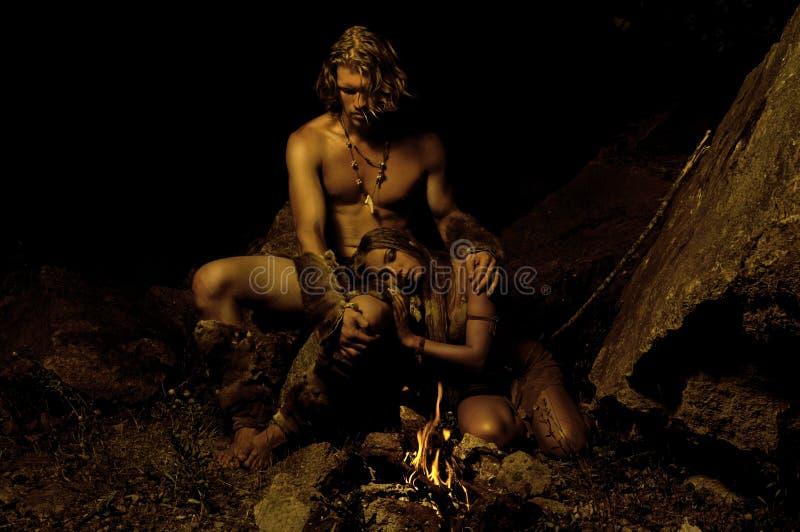 Hombre primitivo y su mujer que se sientan cerca del fuego en la cueva imágenes de archivo libres de regalías