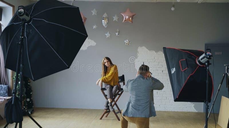 Hombre profesional del fotógrafo que toma la foto de la muchacha modelo hermosa con la cámara digital en estudio foto de archivo libre de regalías