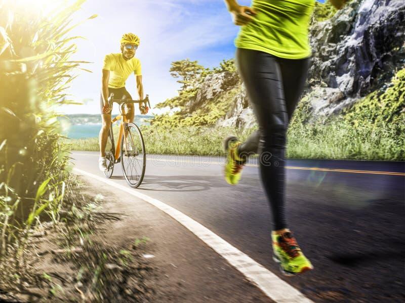 Hombre profesional del triathlon y funcionamiento y ciclyng de la mujer fotos de archivo