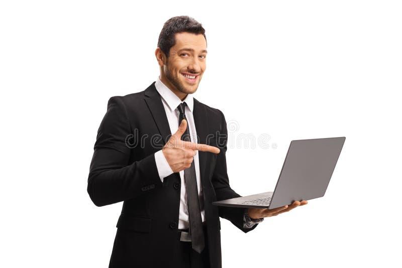 Hombre profesional joven en un traje que sostiene un ordenador portátil y que señala en él imagenes de archivo