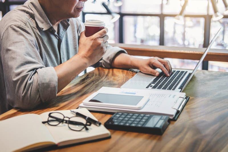 Hombre profesional mayor en la ropa de sport que trabaja usando el ordenador portátil en el café, sosteniendo una taza de café, f fotografía de archivo