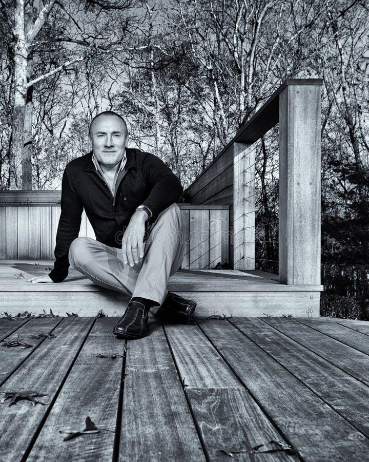 Hombre profesional sentado en decking del jardín imagen de archivo
