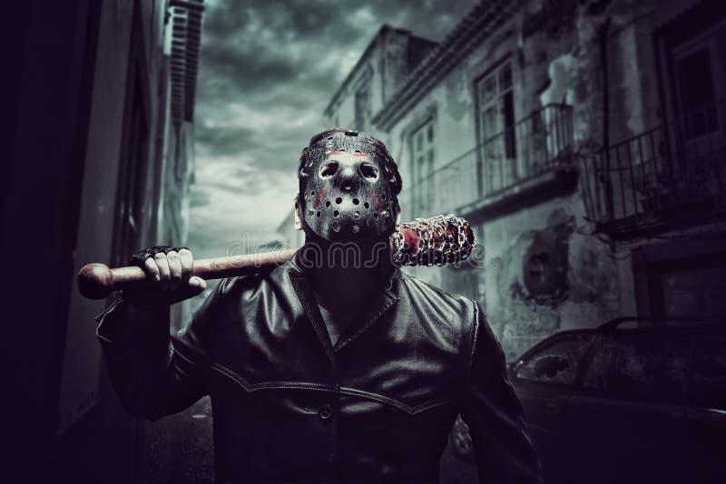 Hombre psico en máscara del hockey con el bate de béisbol sangriento imagenes de archivo